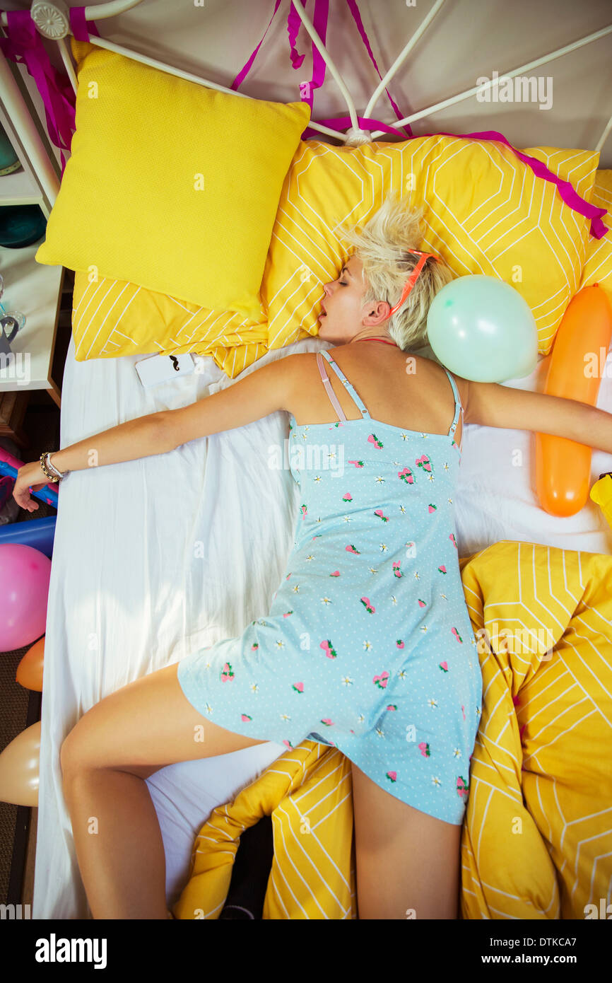 Woman sleeping on bed after party - Stock Image