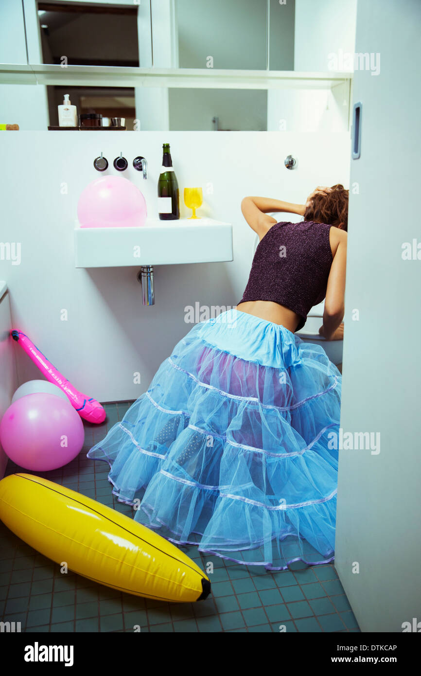 Woman vomiting into toilet at party - Stock Image