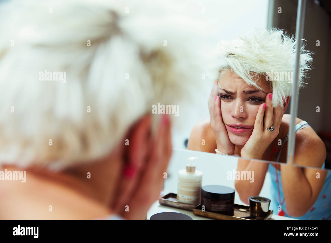 Hungover woman examining herself in mirror - Stock Image
