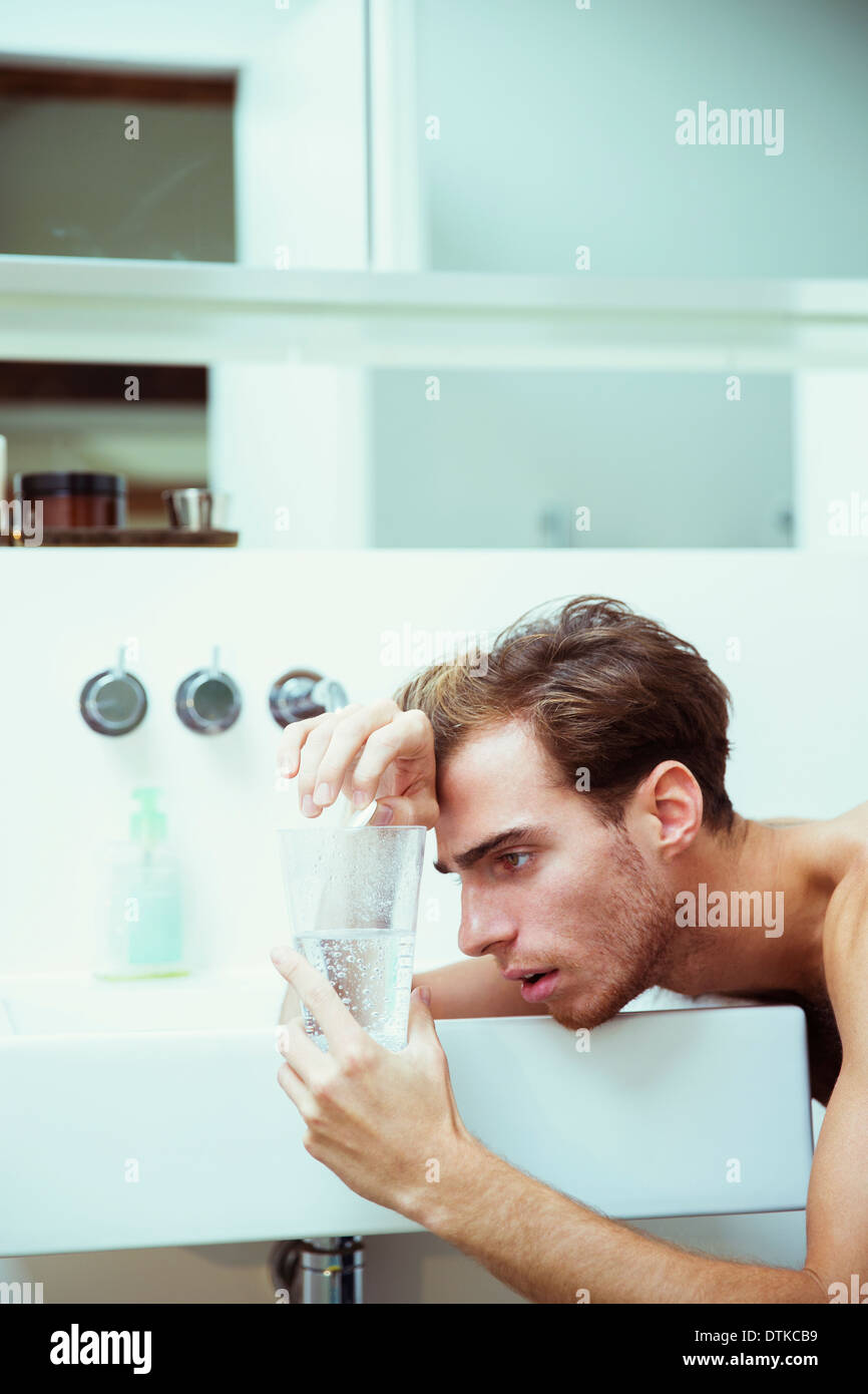 Hungover man watching effervescent tablets in bathroom - Stock Image