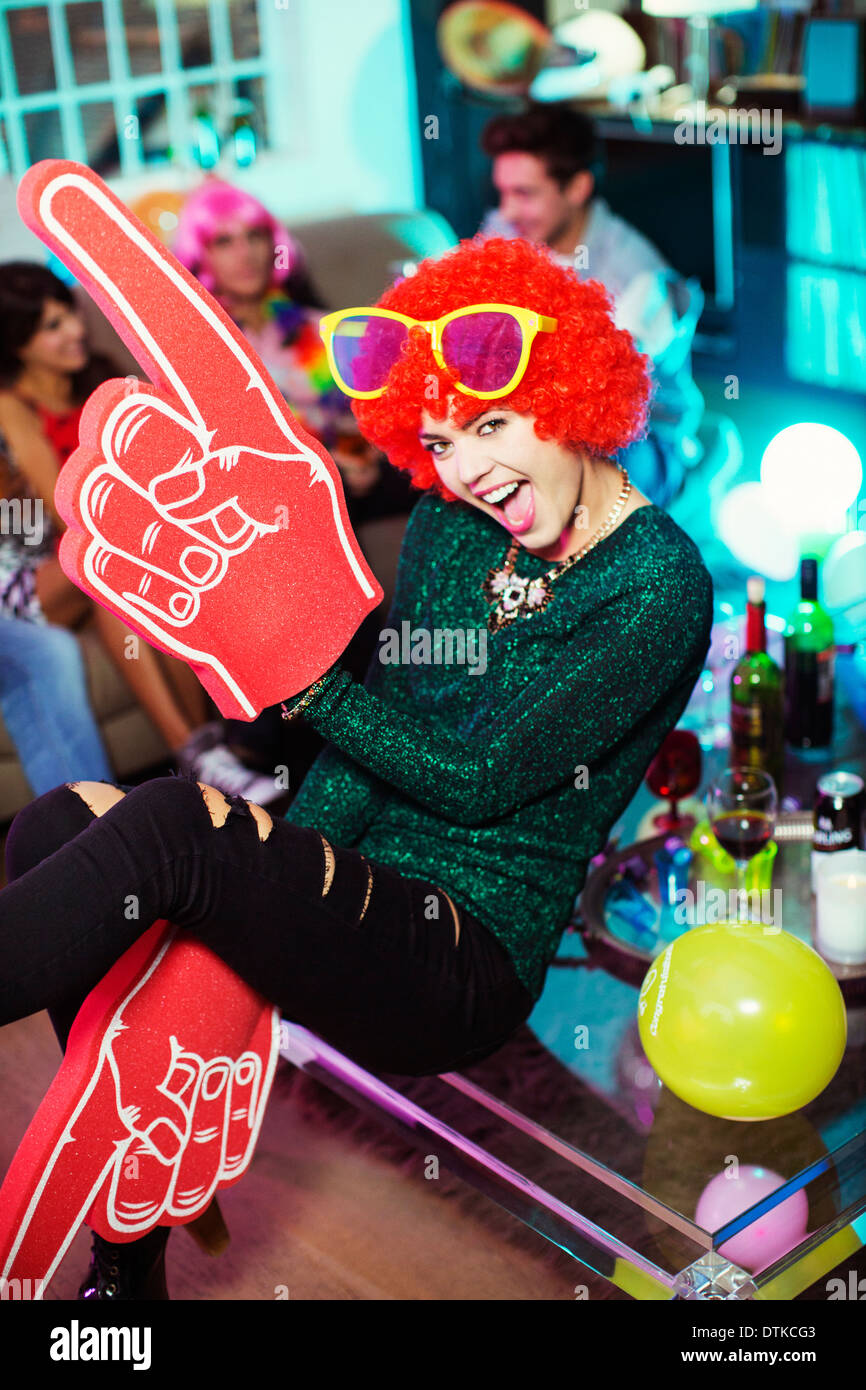 Woman wearing wig, oversized sunglasses and foam finger - Stock Image