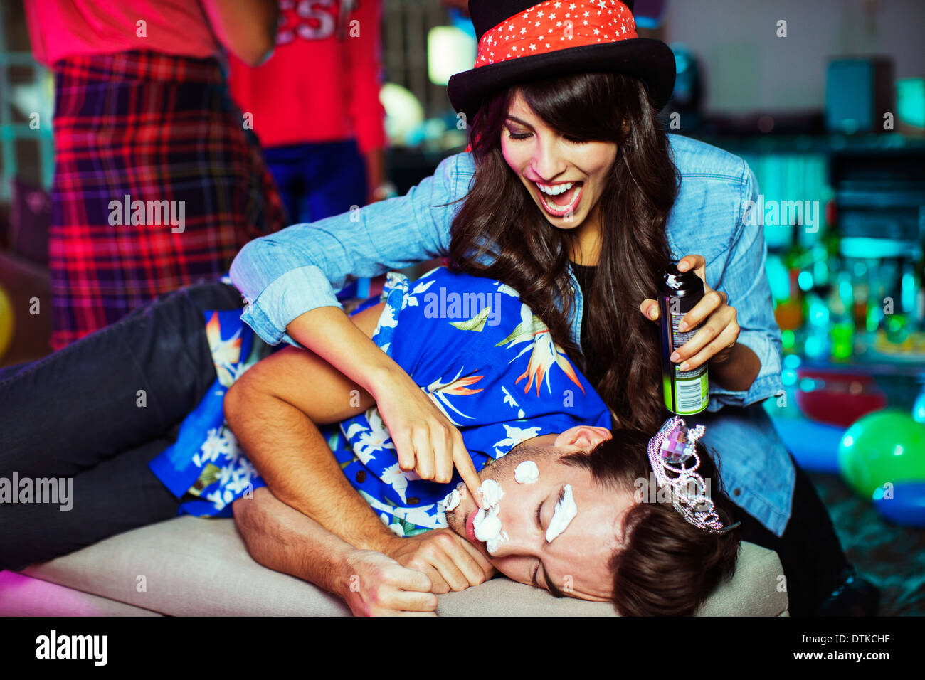 Woman spraying shaving cream on sleeping man's face at party - Stock Image