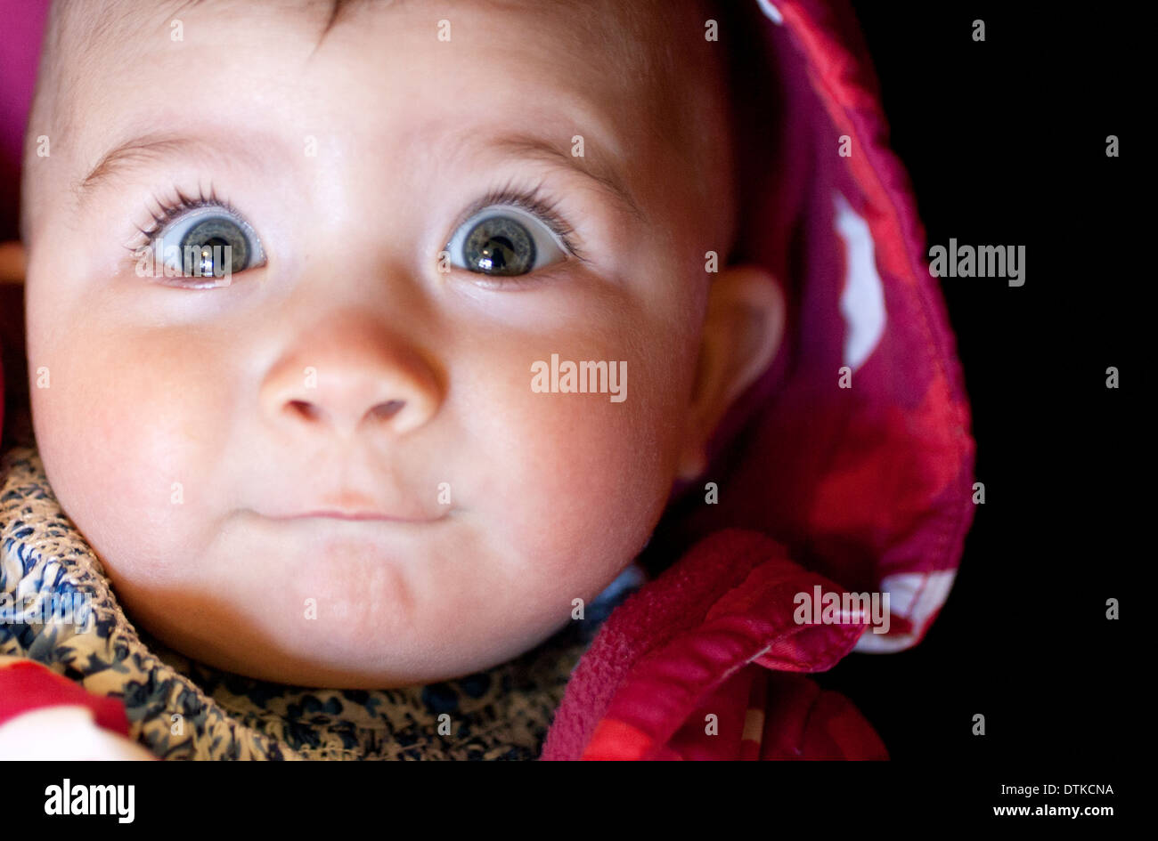 Close up of baby girl's surprised face - Stock Image