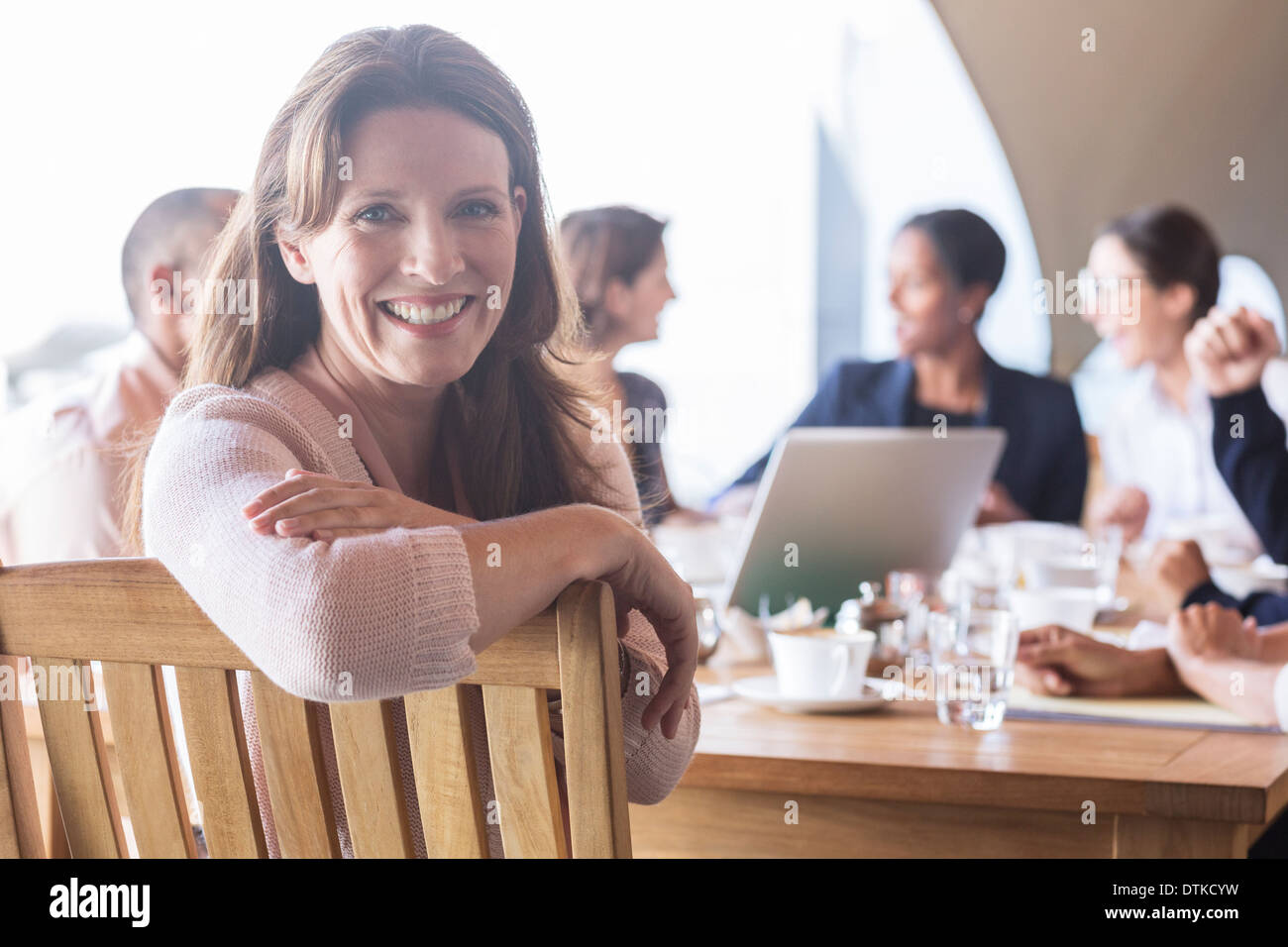 Businesswoman smiling in meeting - Stock Image