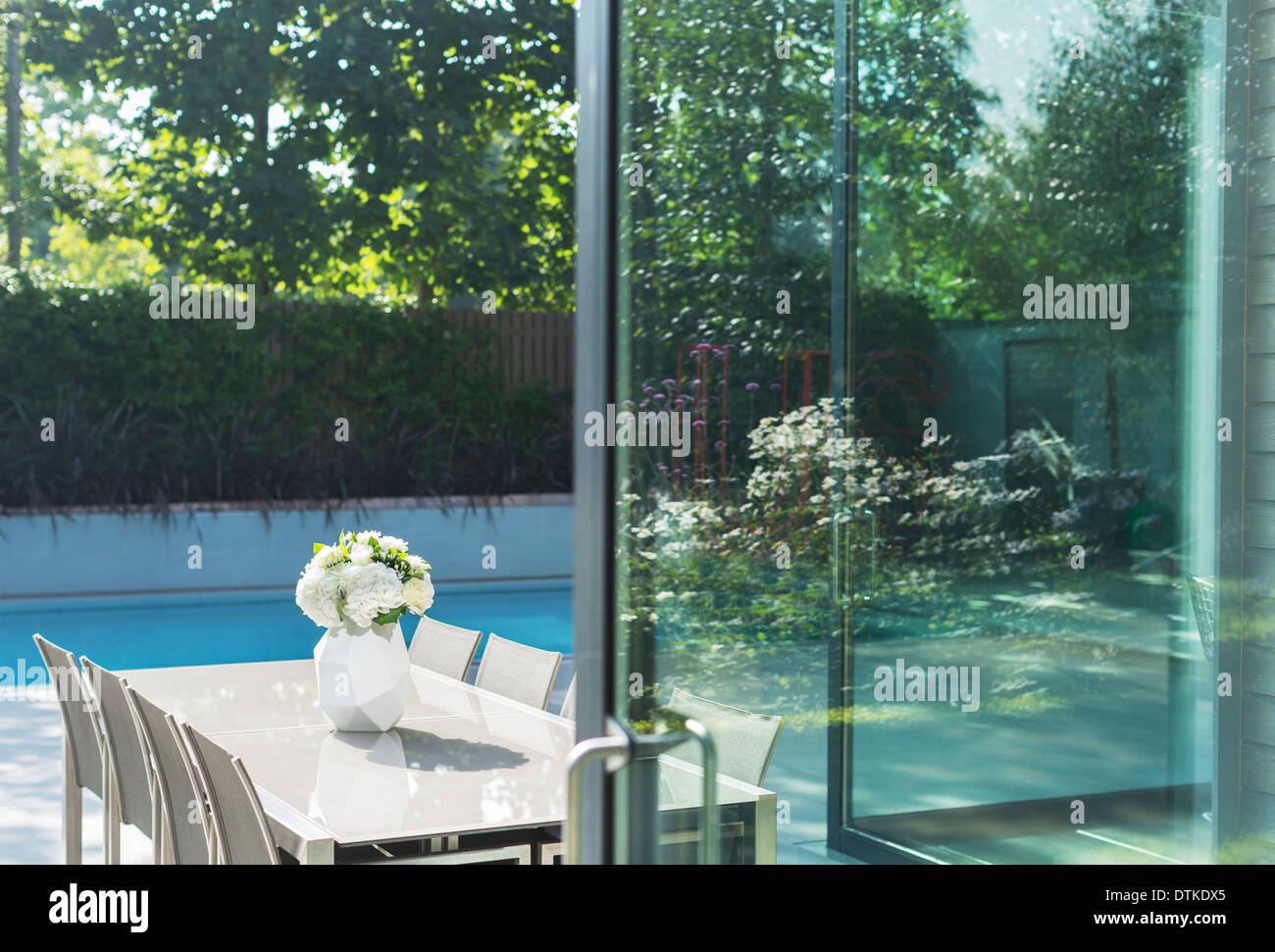 Table and chairs by swimming pool - Stock Image