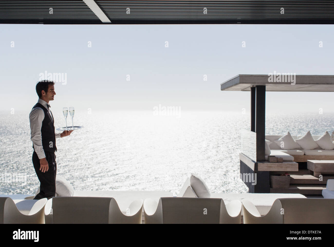 Waiter serving champagne at cabana overlooking ocean - Stock Image