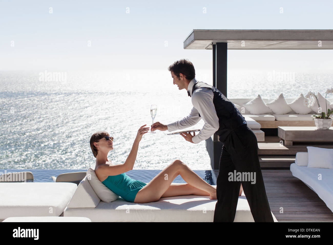 Waiter serving woman drinks outdoors - Stock Image