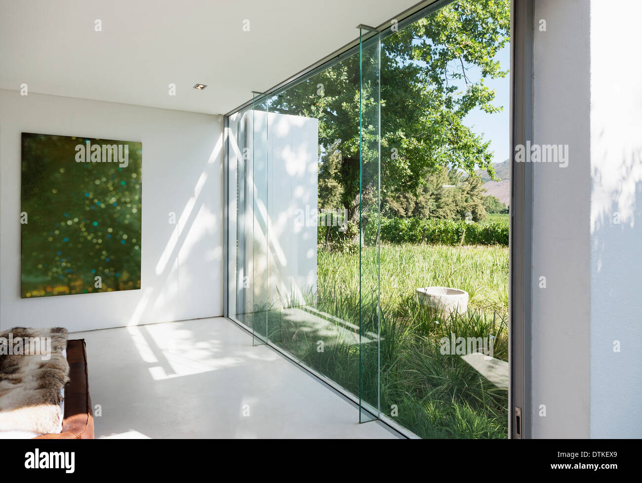 Modern house with glass walls overlooking grass - Stock Image