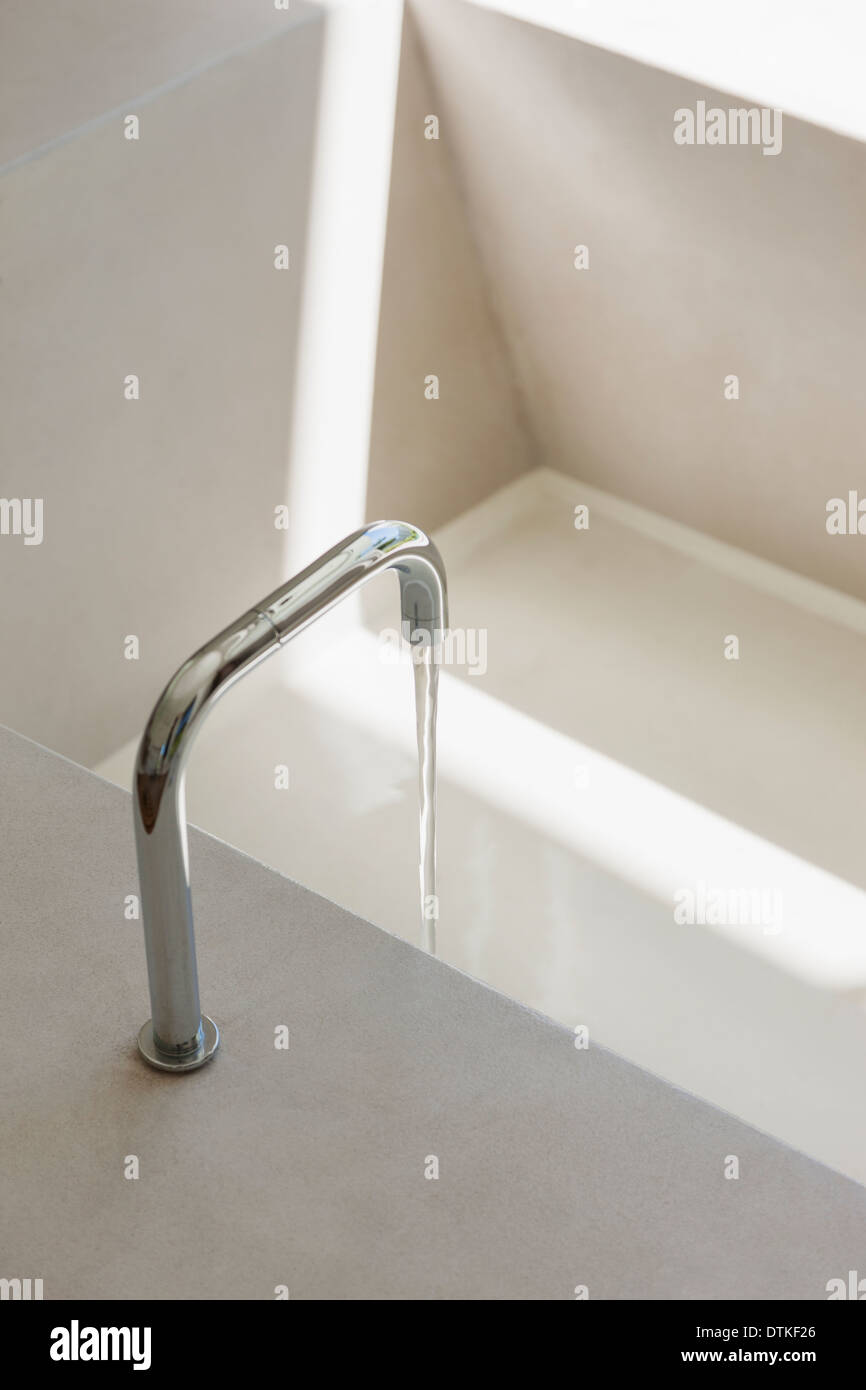 Modern faucet filling bathtub - Stock Image