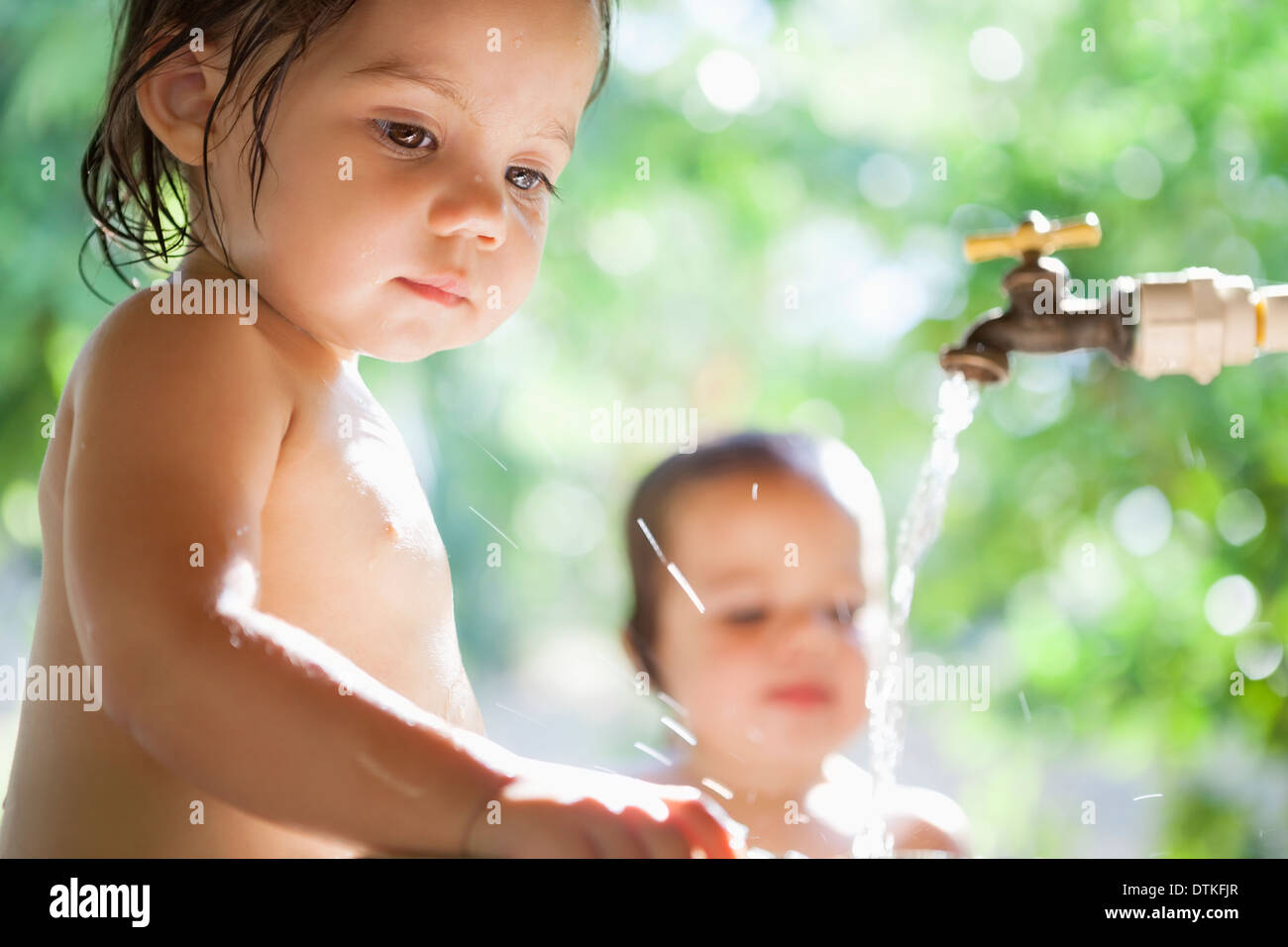 Baby girls playing in water spout outdoors - Stock Image