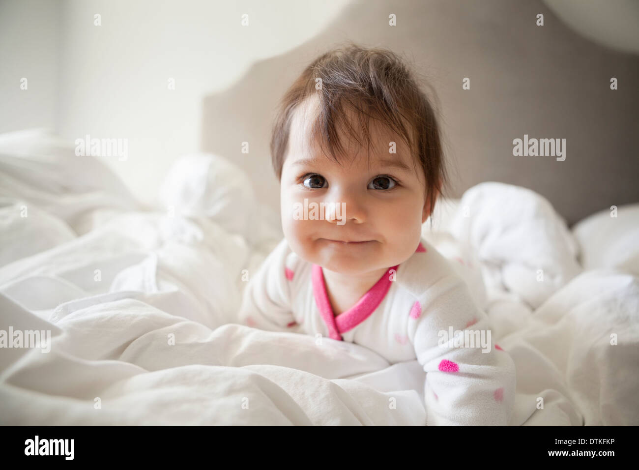 Baby girl crawling in bedsheets - Stock Image