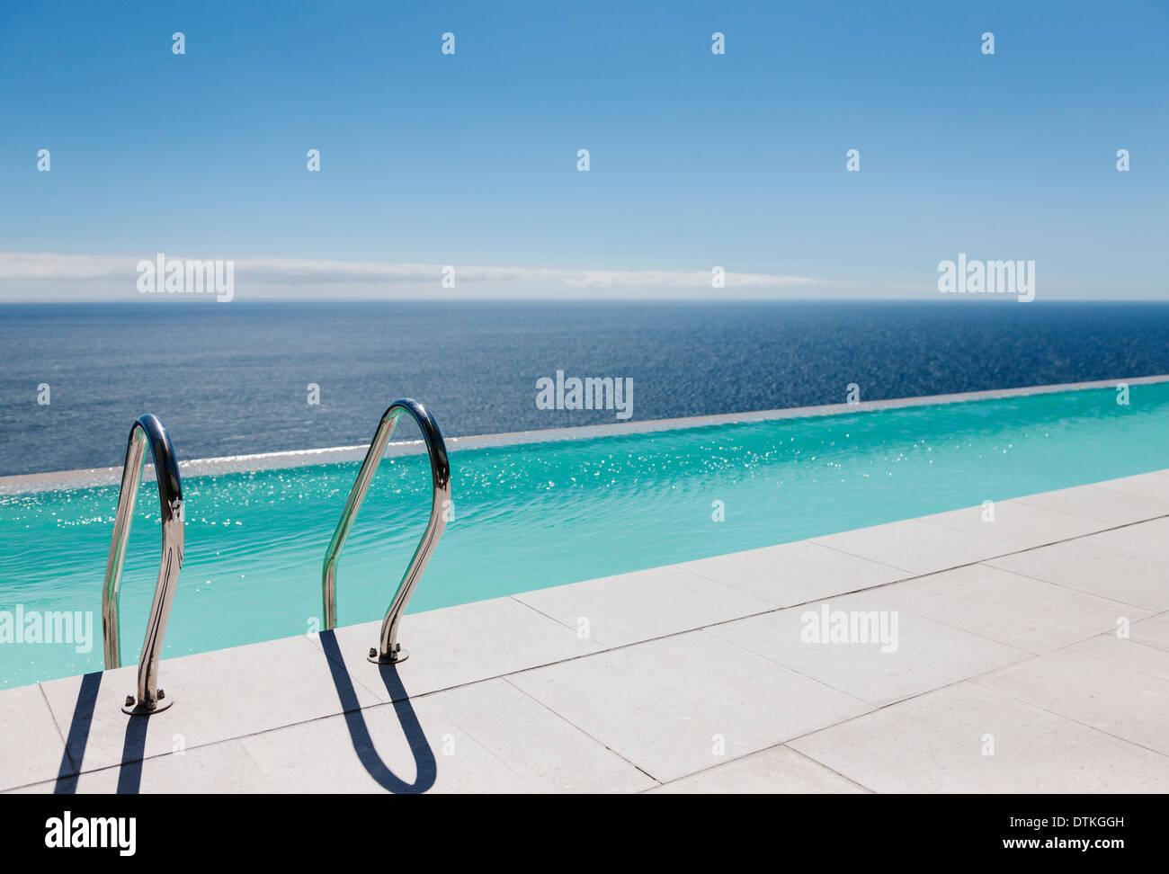 Infinity pool overlooking ocean - Stock Image