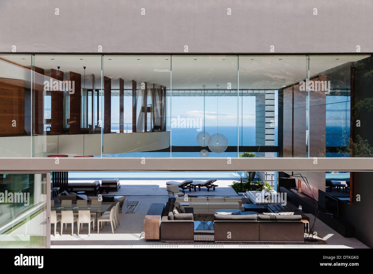 Glass walls of modern house overlooking ocean - Stock Image