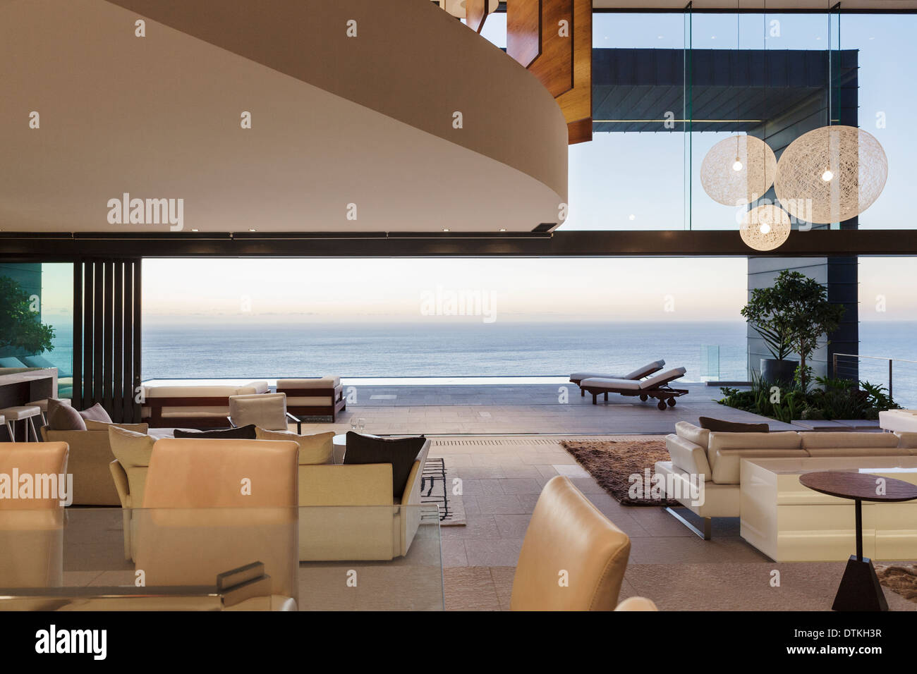 https://c8.alamy.com/comp/DTKH3R/modern-living-room-overlooking-ocean-at-sunset-DTKH3R.jpg