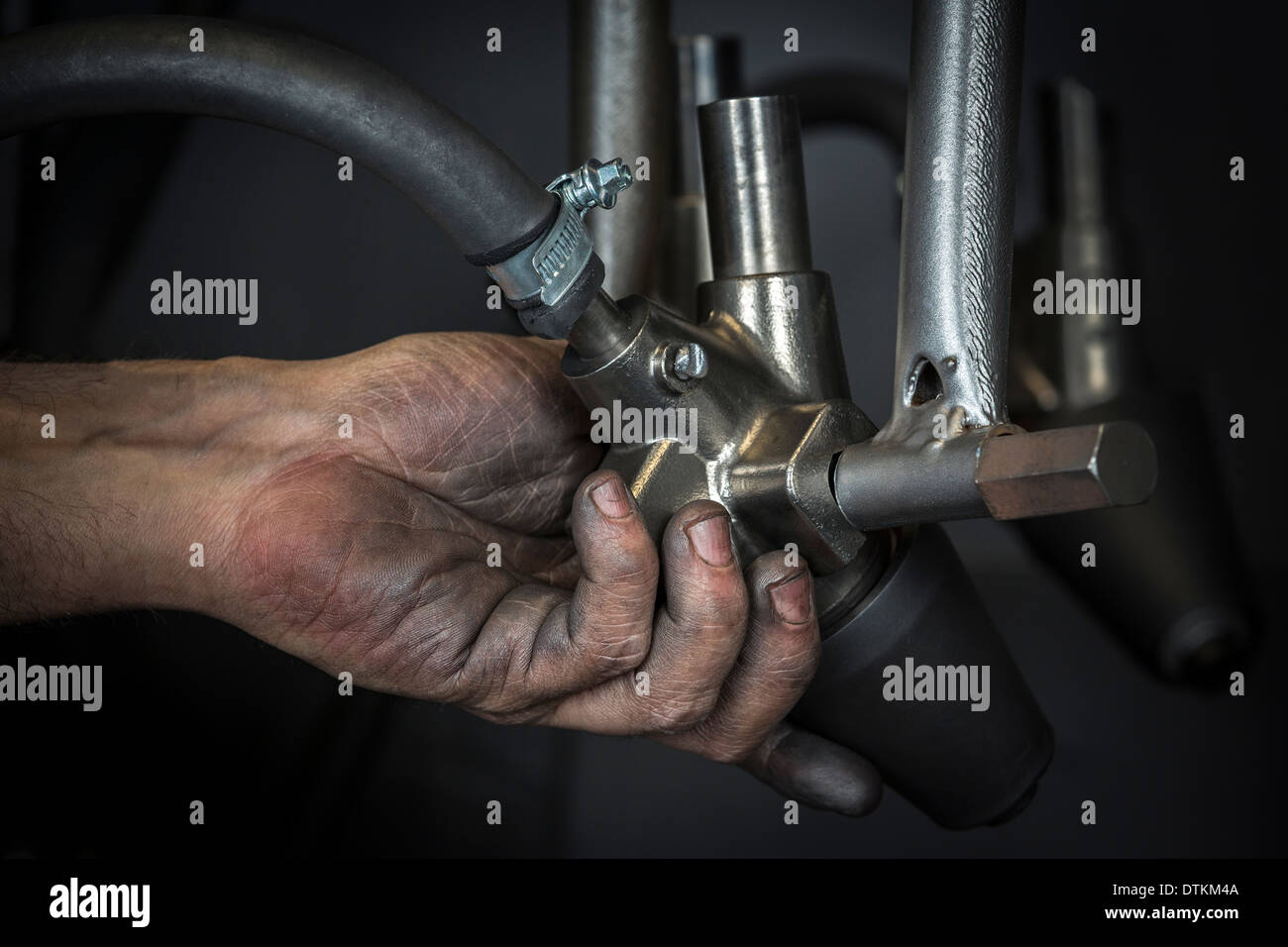 A manual worker's hand. Here an operator positioning a shot blasting machine nozzle. Positionnement d'une buse de grenailleuse. - Stock Image