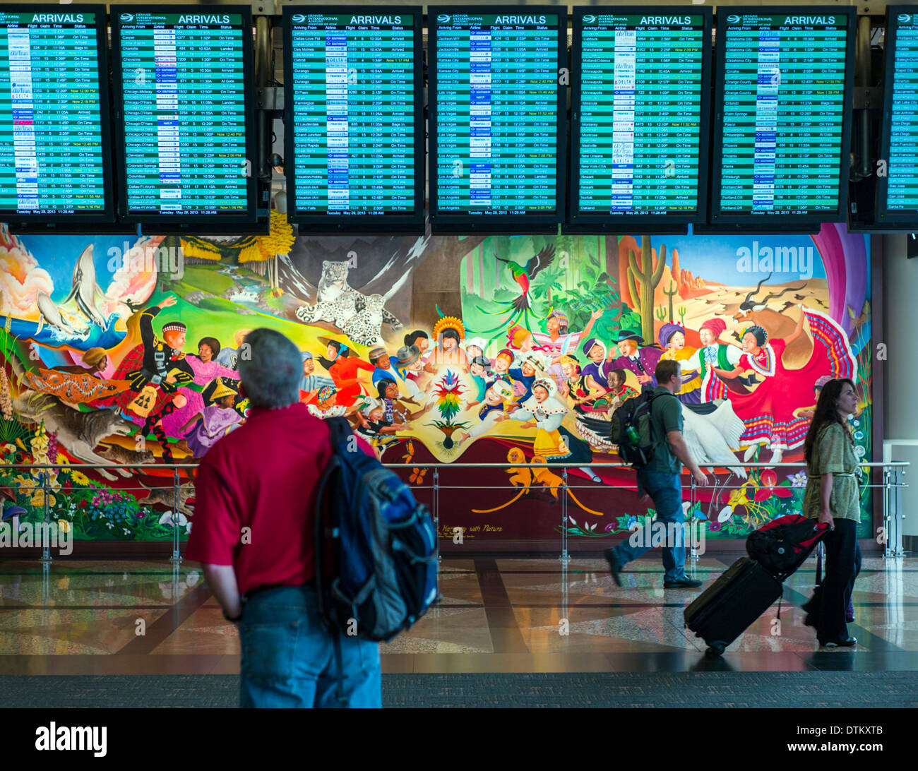 Travelers pass colorful mural titled 'In Peace & Harmony with Nature', by Leo Tanguma, Denver International Airport, Colorado - Stock Image