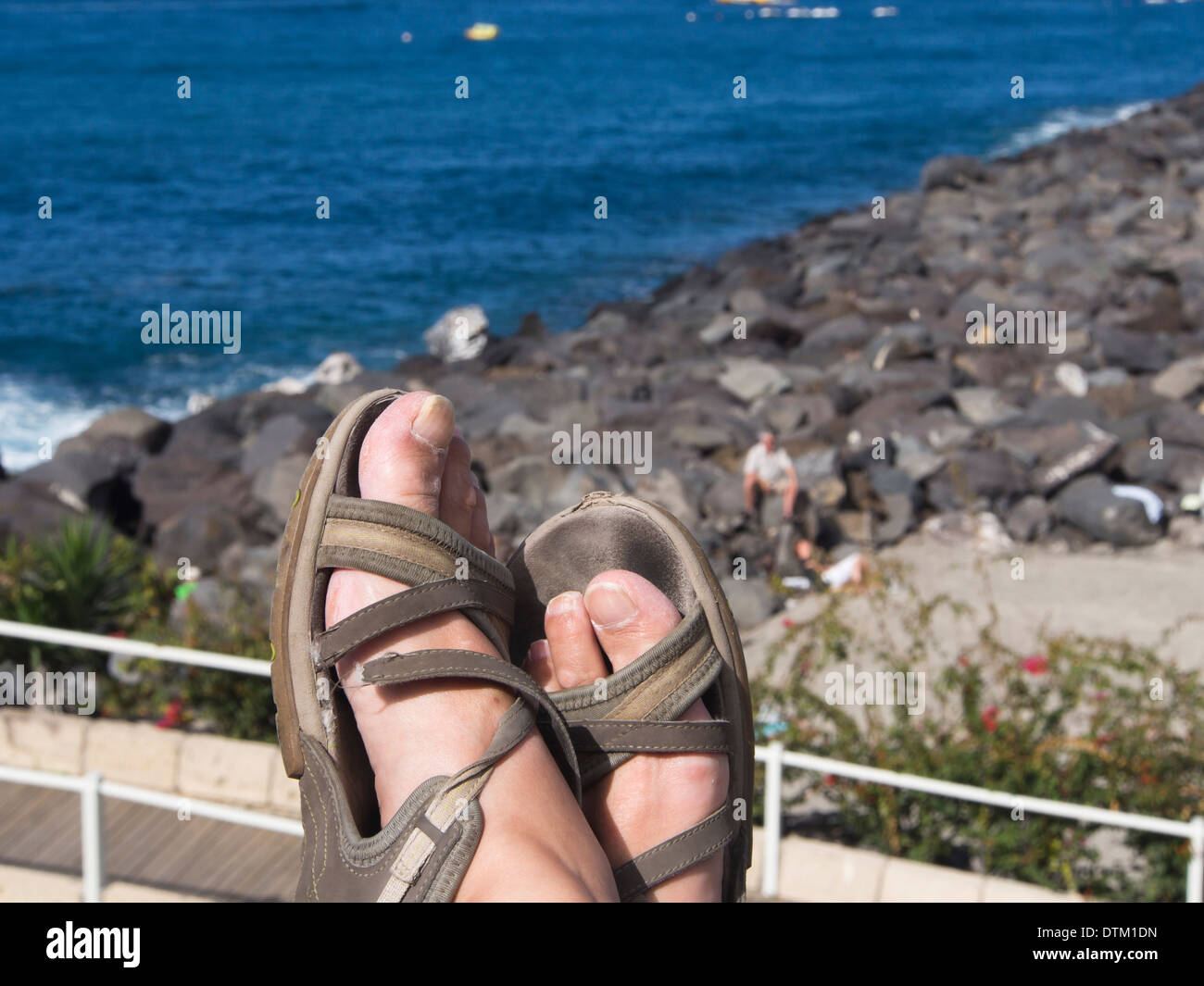 Photographers tired feet and worn out sandals resting along the seaside promenade in Playa Las Americas Tenerife  Spain - Stock Image