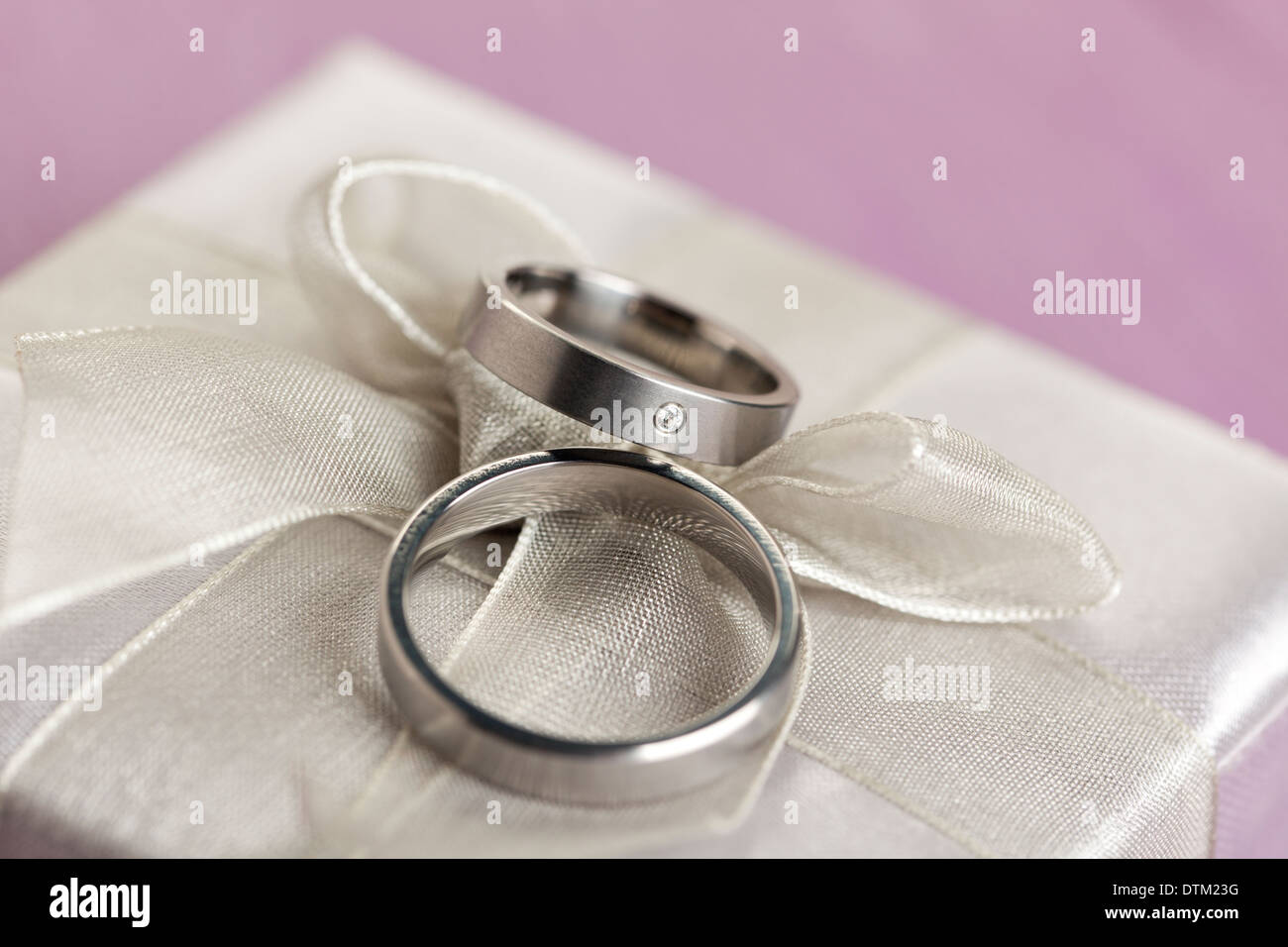 Pair of wedding rings on gift box with silver bow - Stock Image