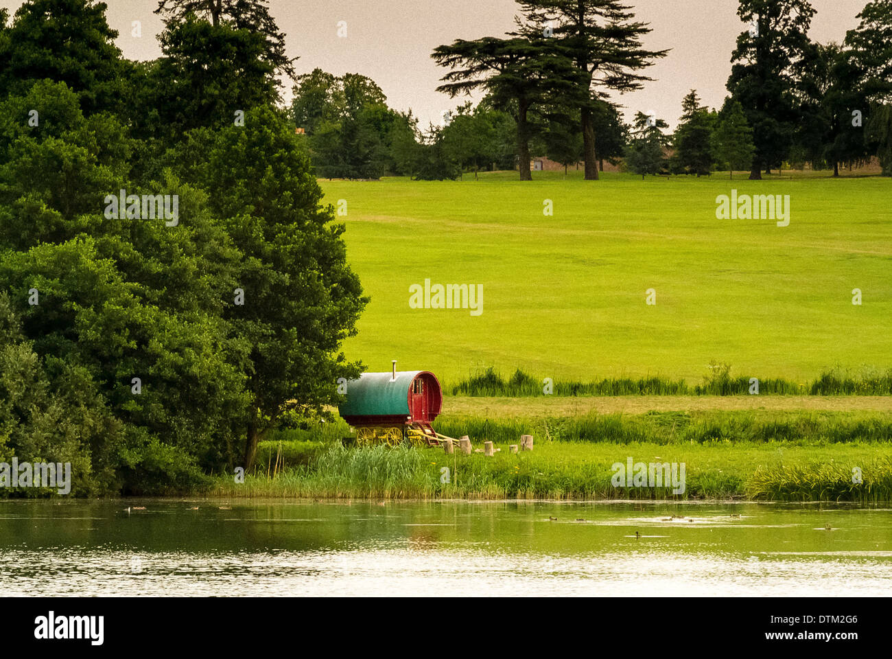 Traditional style Gypsy caravan nestled in trees at side of lake - Stock Image