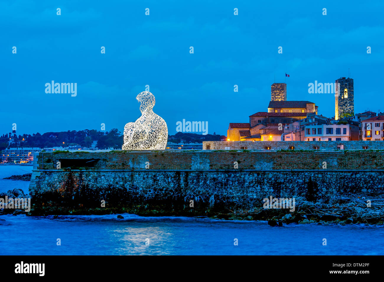 Europe, France, Alpes-Maritimes, Antibes. Old town at dusk and sculpture by Catalan artist Jaume Plensa entitled Nomad. - Stock Image