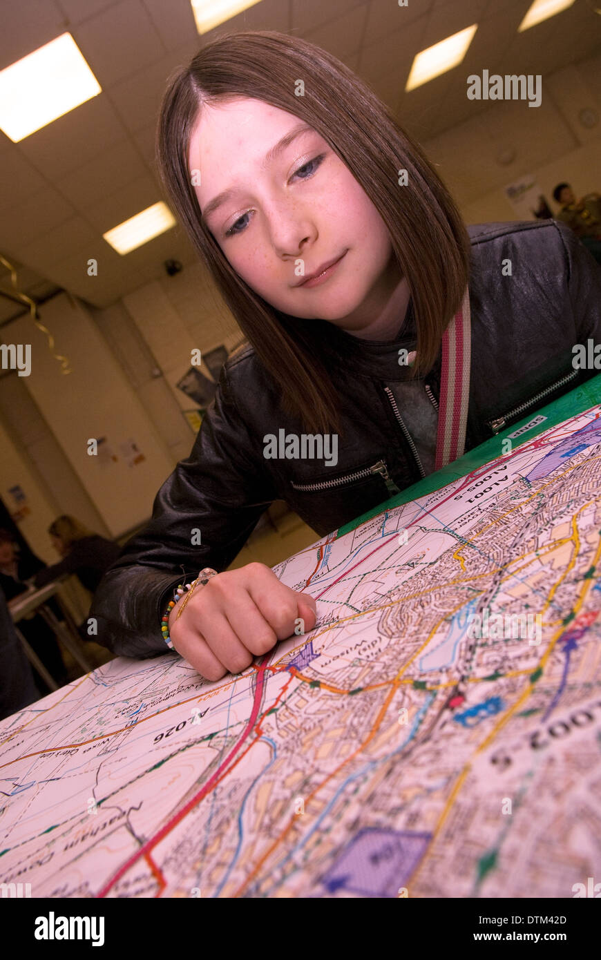 Young girl (12 years old) at a youth event perusing local town plan map as a way to engage young people with local community - Stock Image