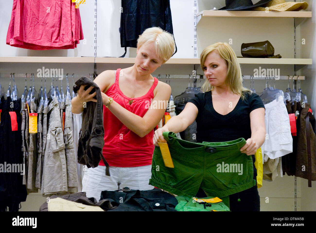 Two women comparing different clothes in shop. Retail store, fashion. Stock Photo