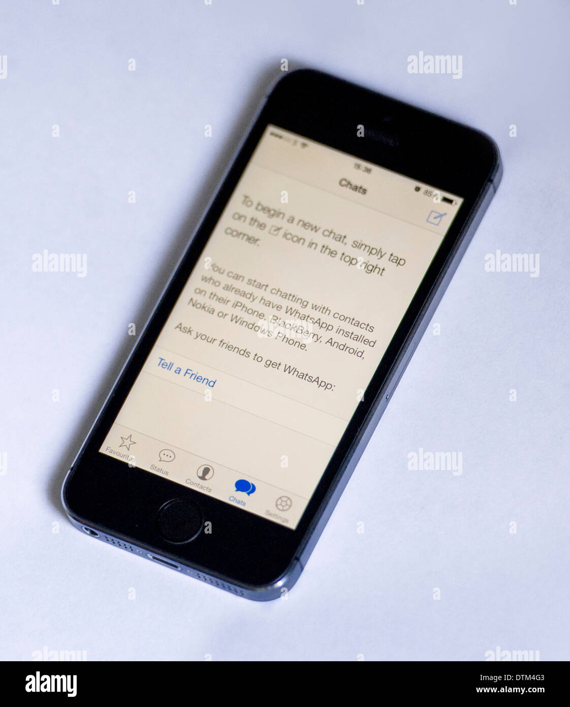 An iPhone 5S on a white  background, showing the Whatsapp app displaying instructions to start a new chat. - Stock Image