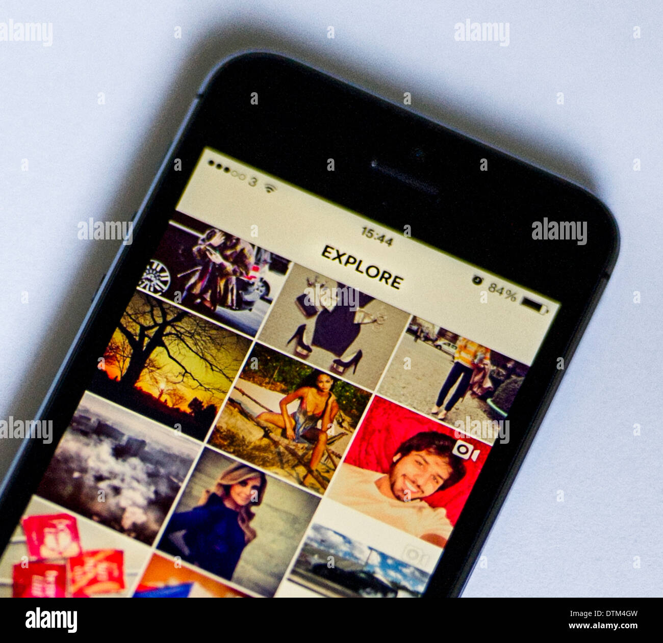 An iPhone 5S on a white  background, showing the Explore page of the Instagram app, which shows some of the most - Stock Image