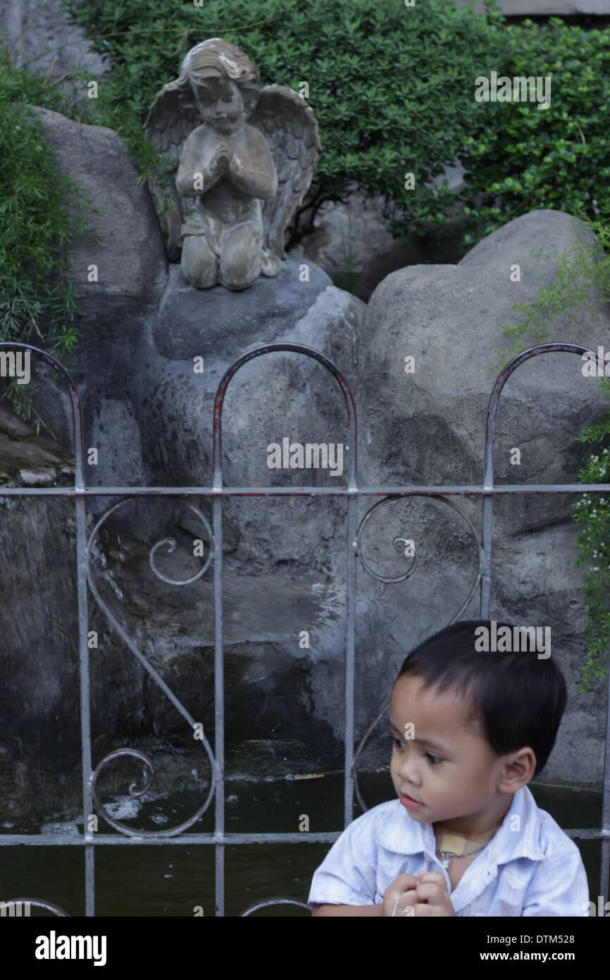 A boy and a statue sharing a prayerful pose - Stock Image