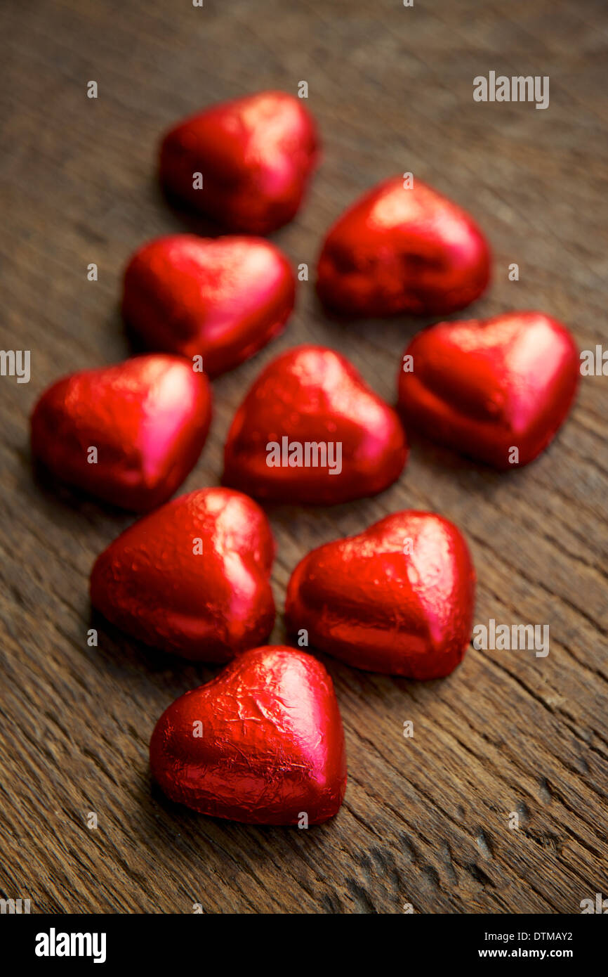 Red foil wrapped chocolate hearts. - Stock Image