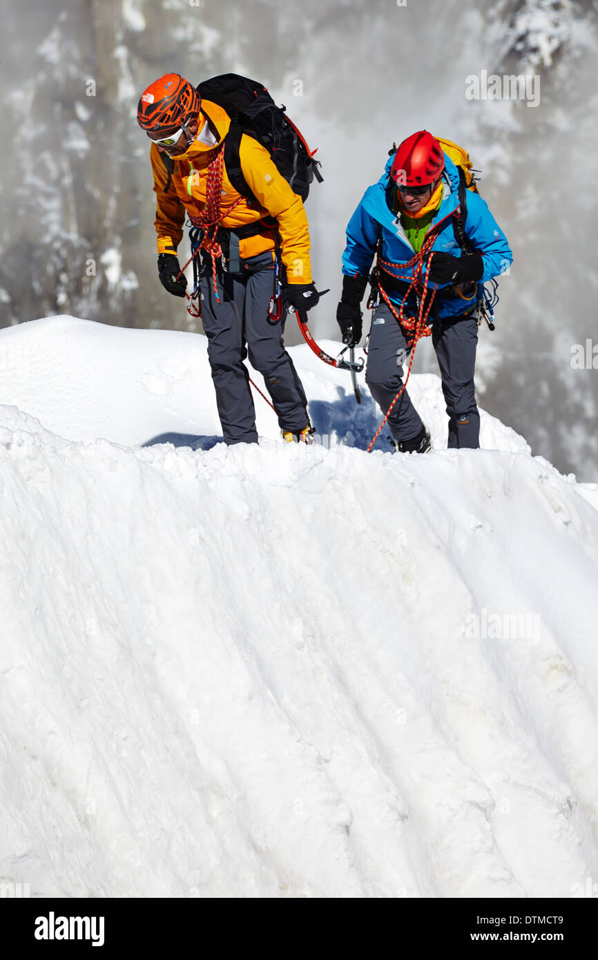 Two climbers returning to the Aiguille du Midi station after climbing Mont Blanc in the French Alps above Chamonix. Stock Photo