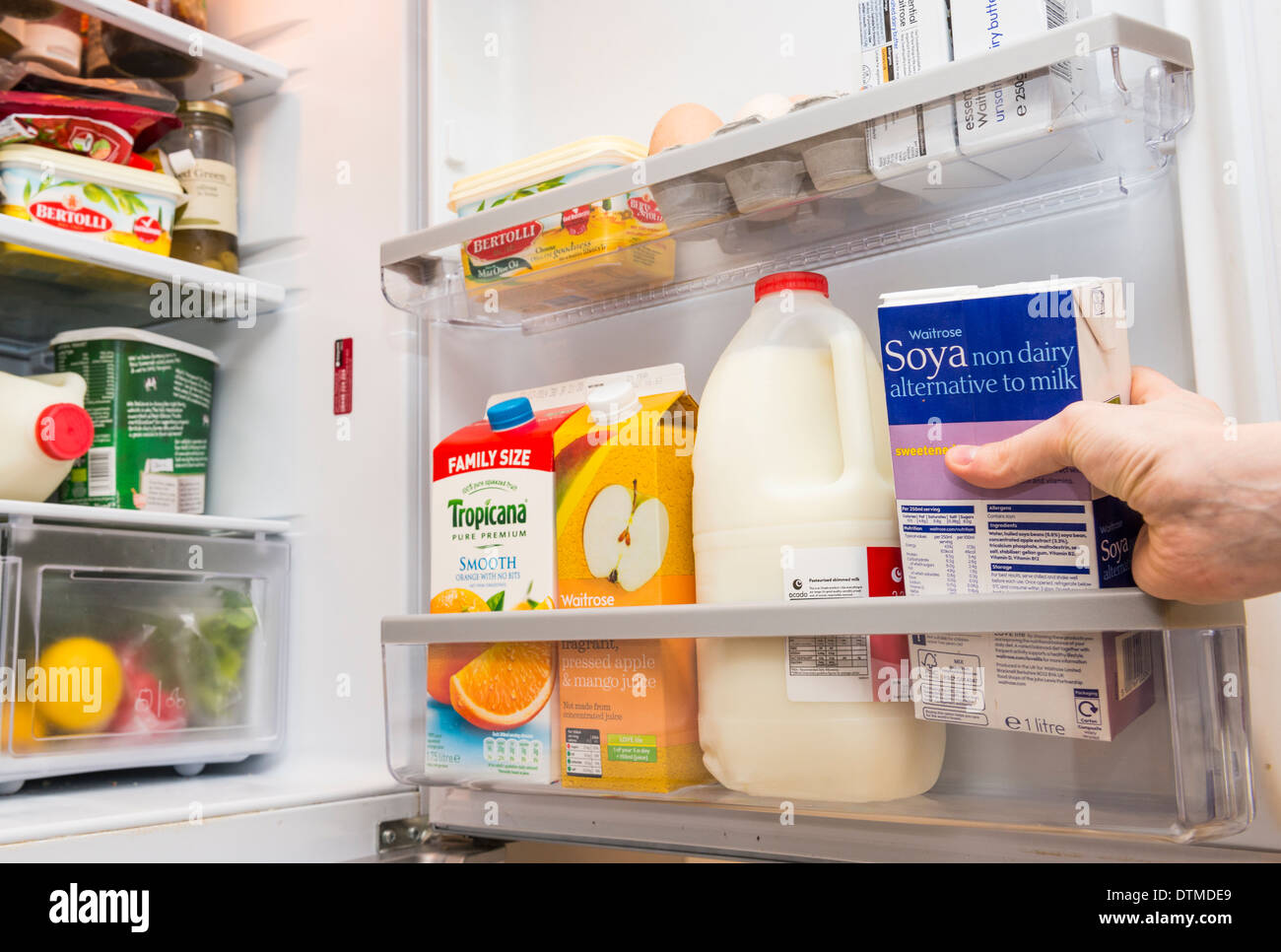 A hand pulling out a carton of soya milk from a fridge door : fridge door - pezcame.com