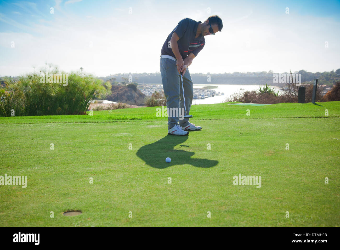 30 year old man putts on the green for a birdie on the golf course - Stock Image