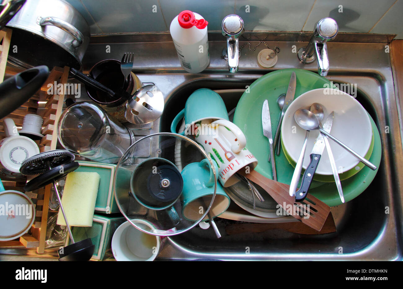 Kitchn sink stacked with dirty pots, England, UK - Stock Image