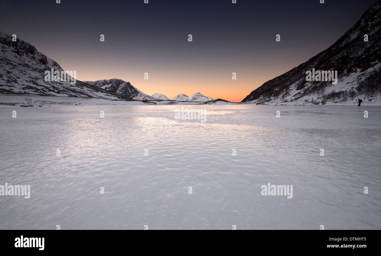 Reflections of the arctic twilight in a frozen fjord near Tromso, Norway - Stock Image
