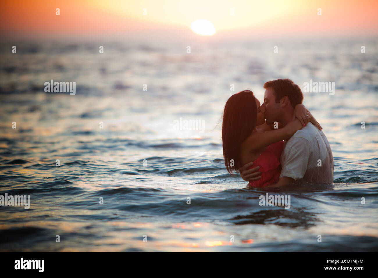 couple kiss and hug in the ocean beach sea during sunset stock photo