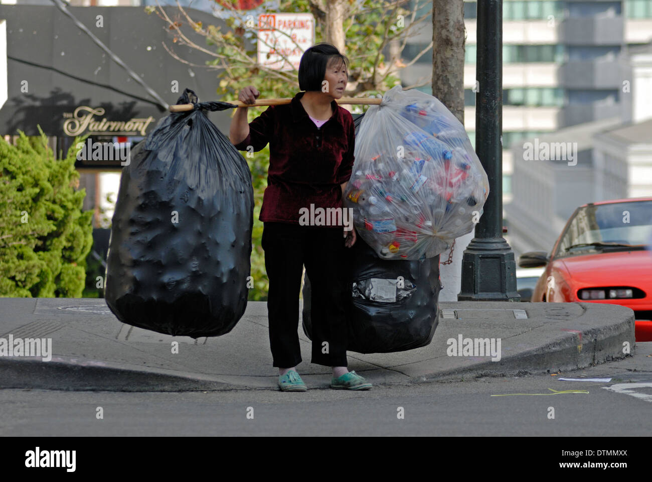 Chinese woman carrying large bags of recyclables on California Street in San Francisco, California. - Stock Image