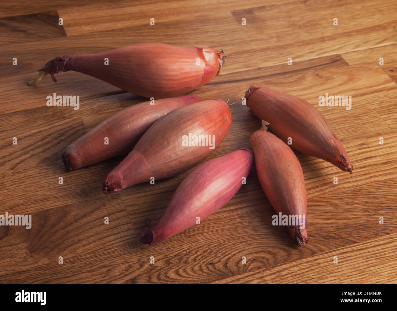 Some shallots on an oak worktop. Stock Photo