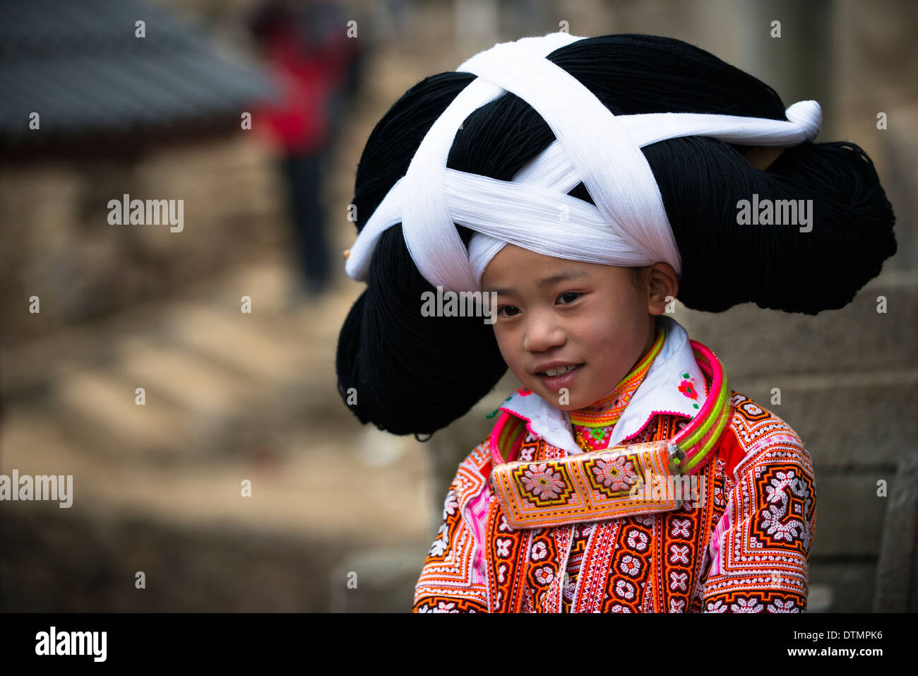 A Long Horn Miao little girl in traditional costumes dancing to celebrate the Tiao Hua festival / spring festival in Guizhou. - Stock Image