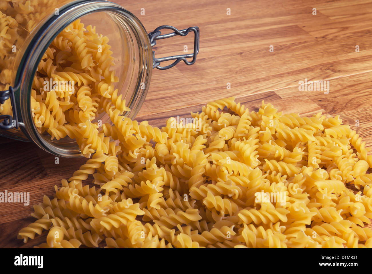 Some fussily pasta spilling from a jar. - Stock Image