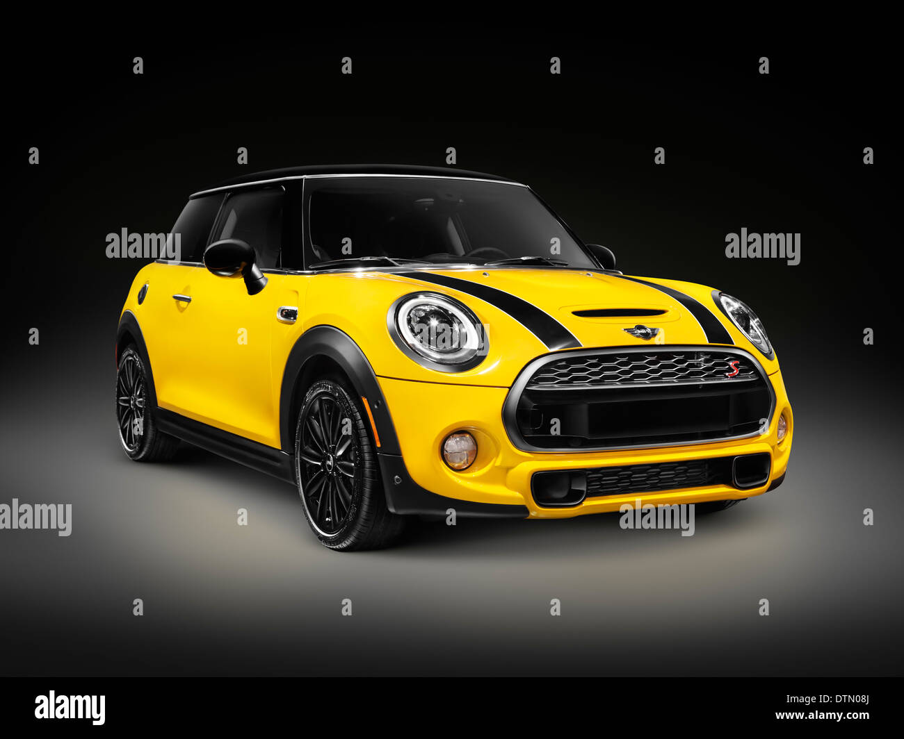 Yellow 2014 Mini Cooper S, Mini Hatch, hatchback compact city car isolated on black background - Stock Image