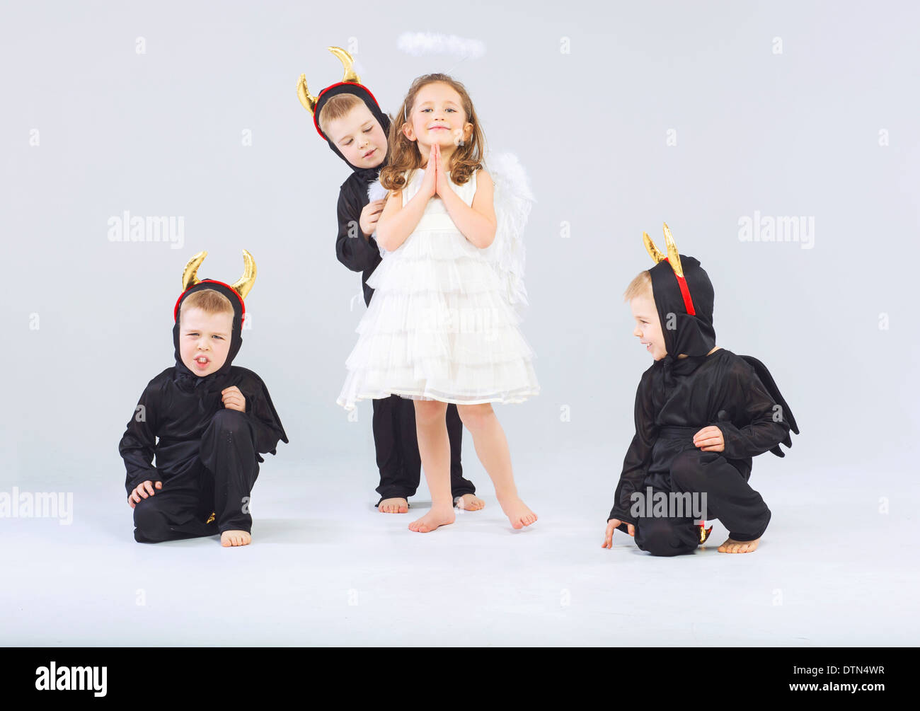 Little angel and three cute devils - Stock Image