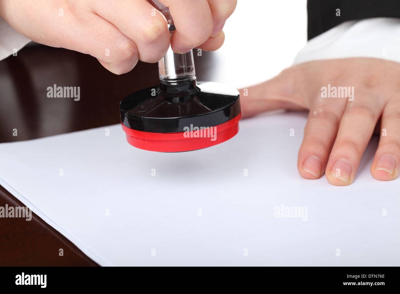 Female hand making chop on a document for approval - Stock Image