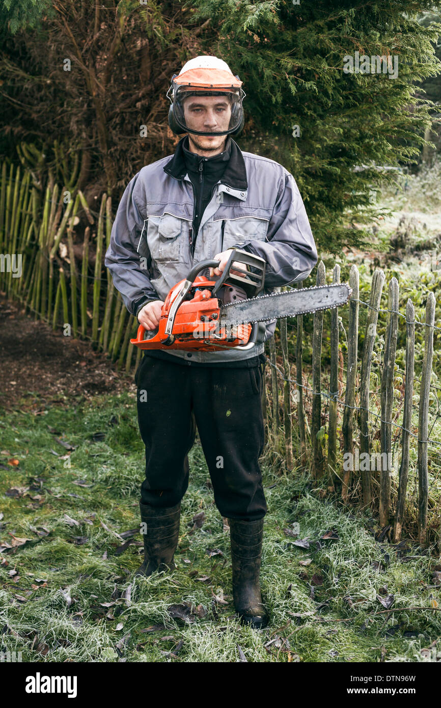 Portrait of professional gardener with chainsaw standing in the garden. Stock Photo