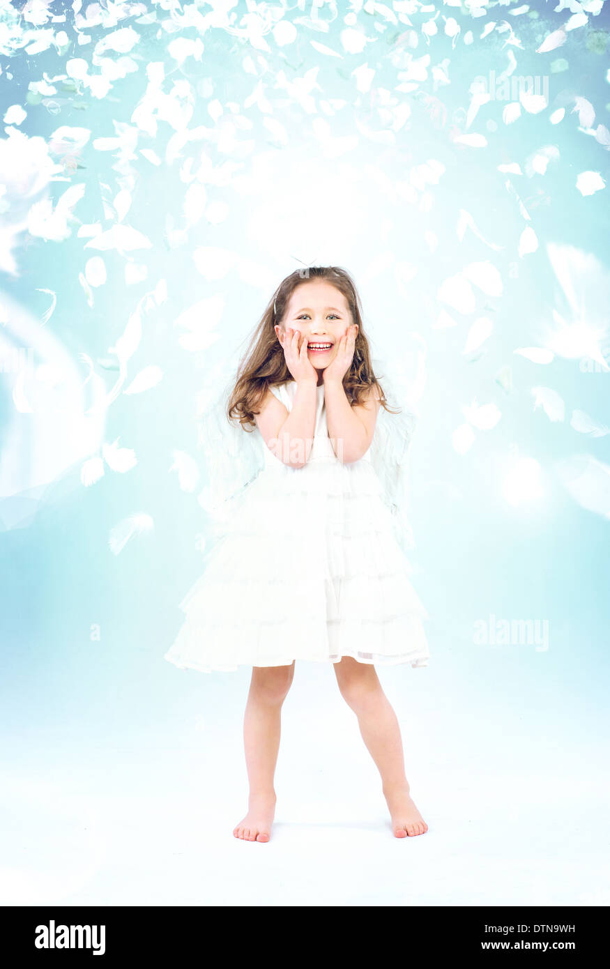 Cute little girl among flying rose petals - Stock Image