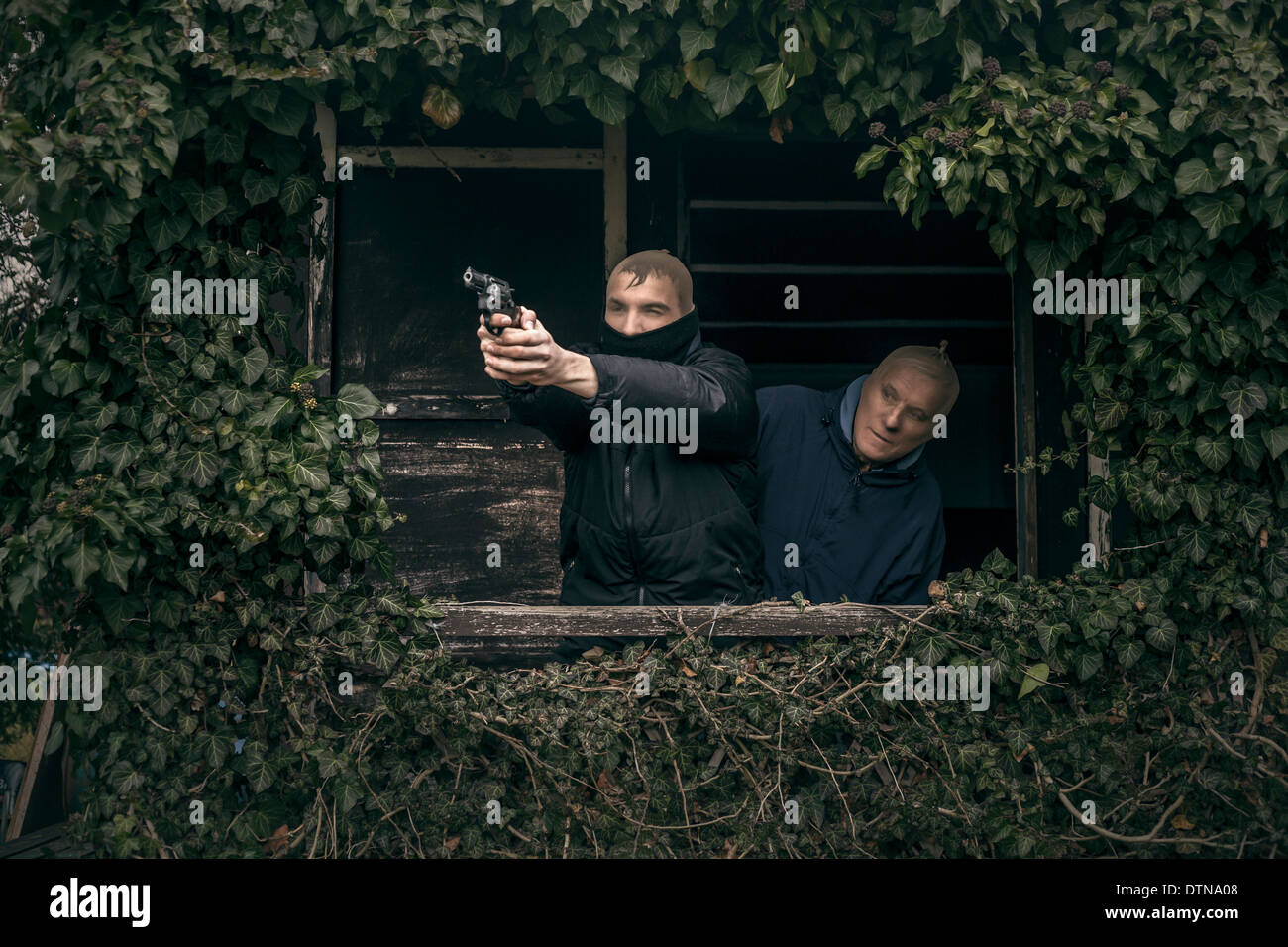 Two masked armed men hiding on overgrown porch of old cabin. - Stock Image