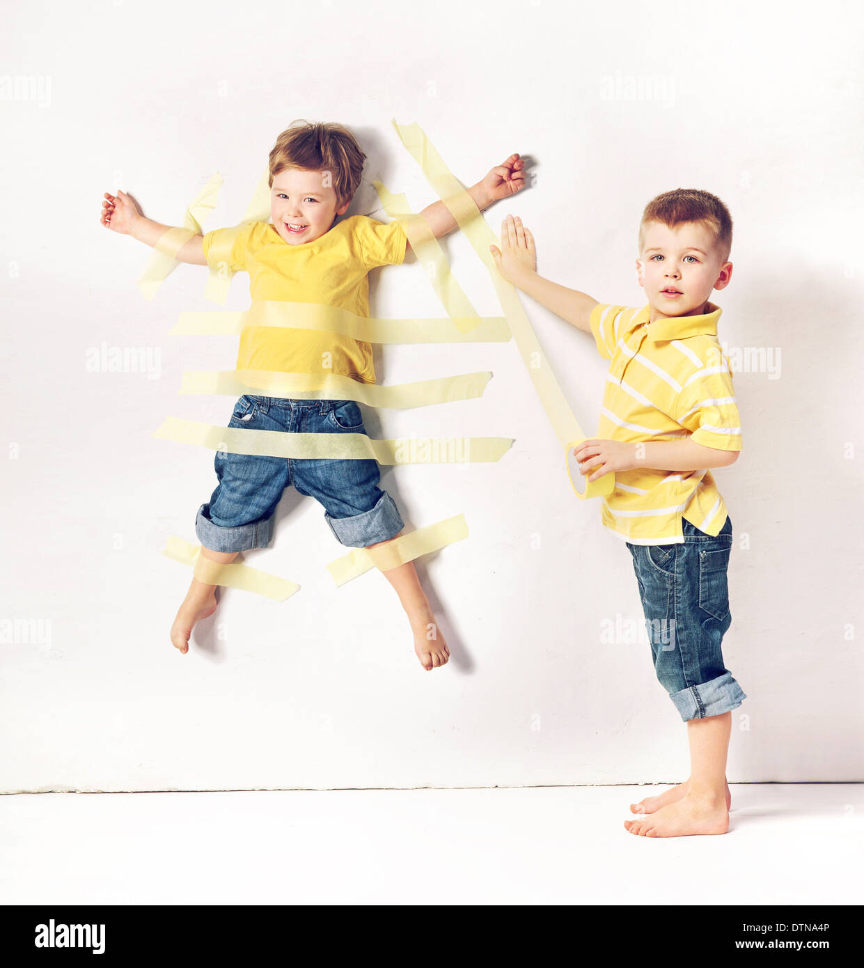 Two cute little brothers having great fun - Stock Image