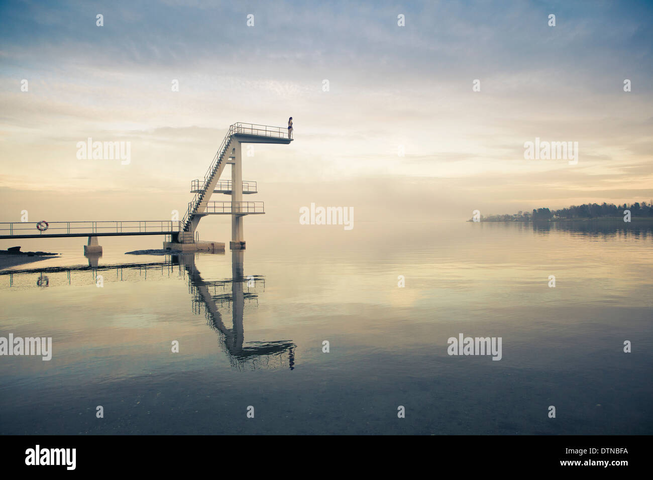 Girl diver stands on diving platform about to dive into beautiful lake - Stock Image
