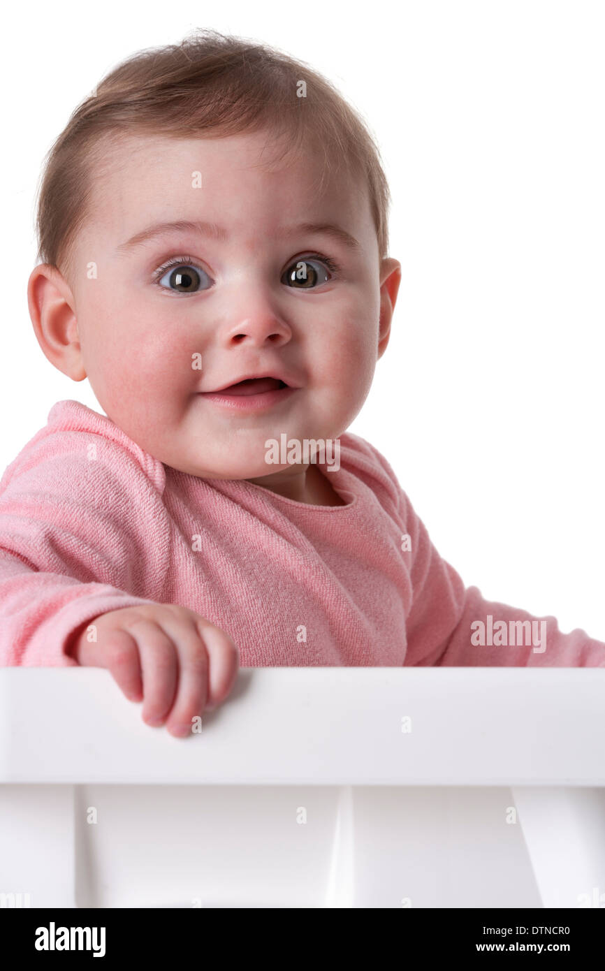 Portrait of a baby girl with large brown eyes on white background