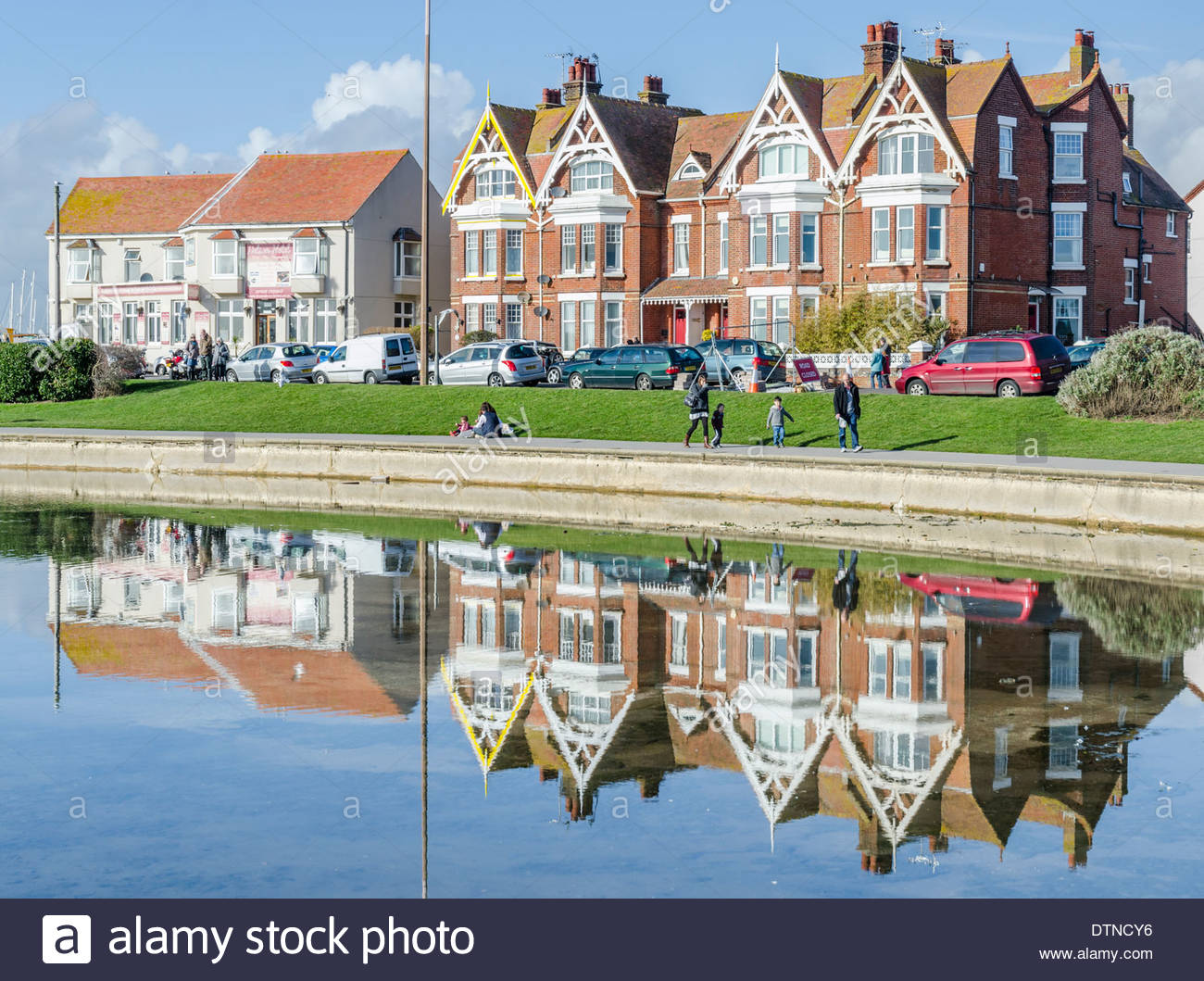 Victorian housing with reflections in nearby lake. - Stock Image